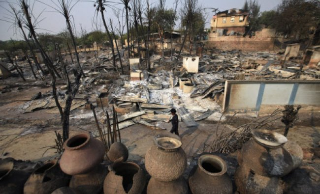 A man walks past homes burned down during the riot in Meikhtila March 23, 2013. Myanmar declared...