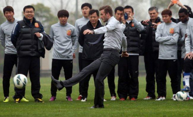 Football superstar David Beckham (C) illustrates his skills during a visit to the Zall Football...