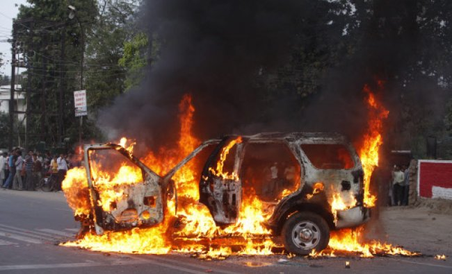 A vehicle stands in flames after it was set on fire by lawyers in Allahabad...