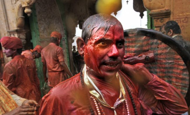 A villager from Barsana smeared with colors arrives at the Nandagram temple...