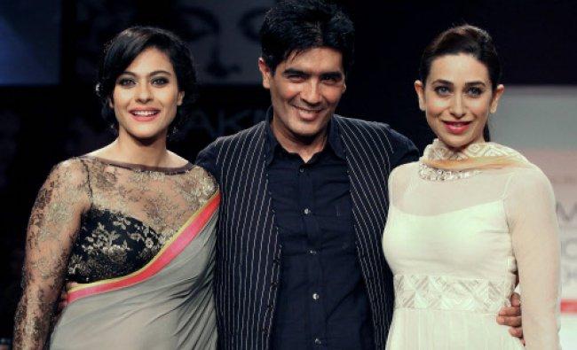 Film actresses Kajol Devgan (L) and Karishma Kapoor showcase creations by designer Manish Malhotra..