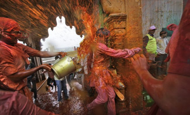 Villagers from Nandgaon throw colored water on the villagers from Barsana as they arrive at the...
