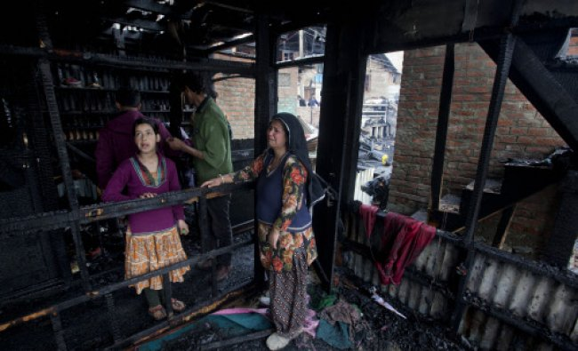 A Kashmiri woman cries as her daughter inspects their damaged shanty after it was gutted in fire...