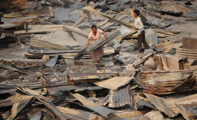 Buddhist people search the remains of their burnt houses in riot-hit Meiktila on March 23, 2013.