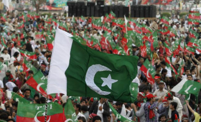 Supporters of the political party Pakistan Tehreek-e- Insaf (PTI) wave national and party...