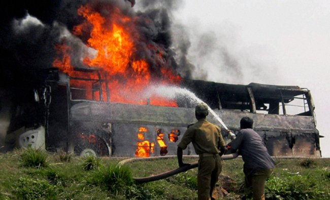 Fire fighters trying to douse fire after a bus carrying Sri Lankan tourists cought fire in Motihari