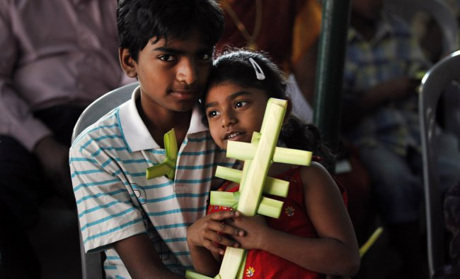 Christian children attend the Palm Sunday mass at St. Pauls Church in Bangalore...