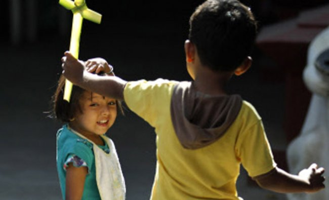 Children play with crosses made of blessed palm during a Palm Sunday Mass in Bangalore...