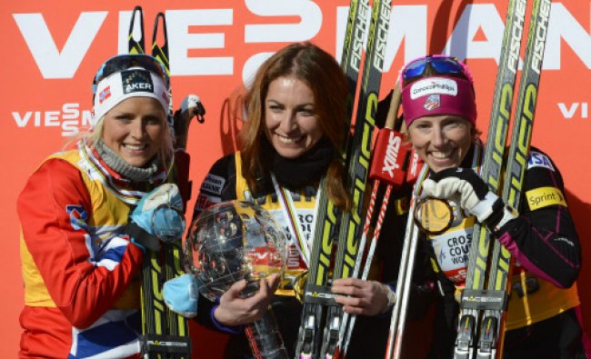 Poland\'s Justyna Kowalczyk holds her overall World Cup trophy next to second placed...