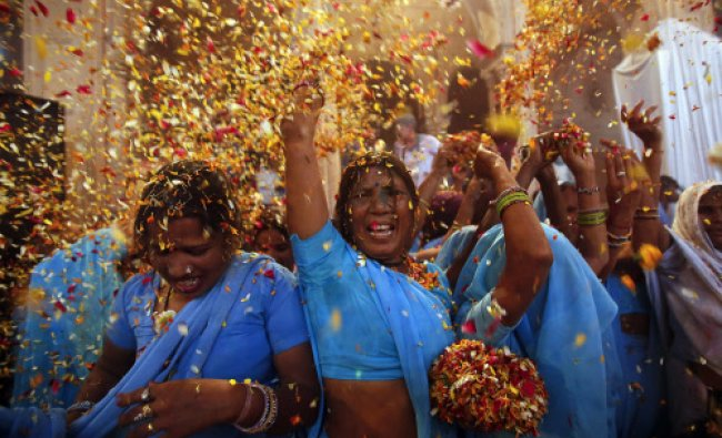 Women throw flowers into the air during a holi celebration at the Meera Sahavagini ashram...