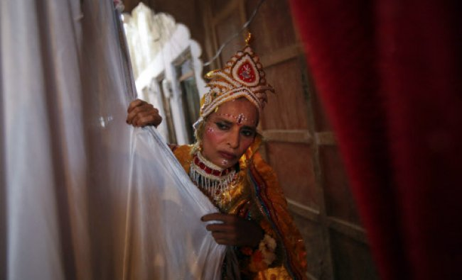 A woman dressed as the Hindu goddess Radha looks out from behind a curtain during a holi celebration