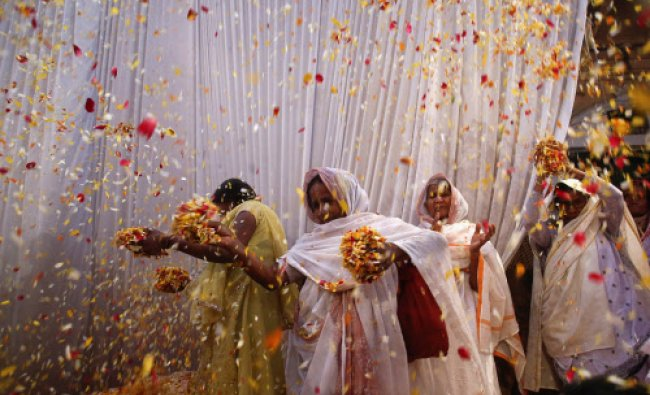 Widows throw flowers into the air during a holi celebration at the Meera Sahavagini ashram...