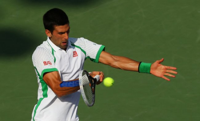 Novak Djokovic of Serbia returns a shot to Somdev Dewarman of India during Day 7 of the Sony Open...