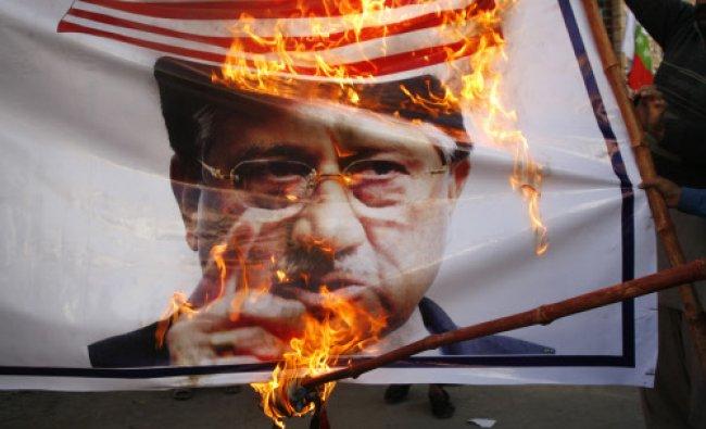 Supporters of Awami Majlis-e-Amal Pakistan (AMAP) burn an image of former President...