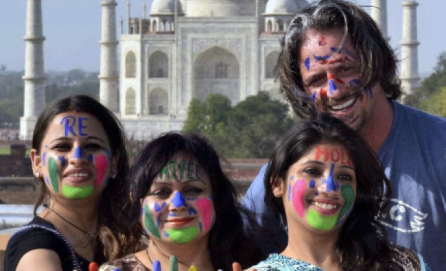 Girls with coloured face pose for photograph along with foreign tourists ahead of festival of colour