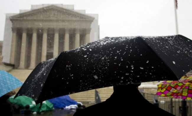 A man stands under an umbrella in a light, wet snowfall in front of the Supreme Court building...