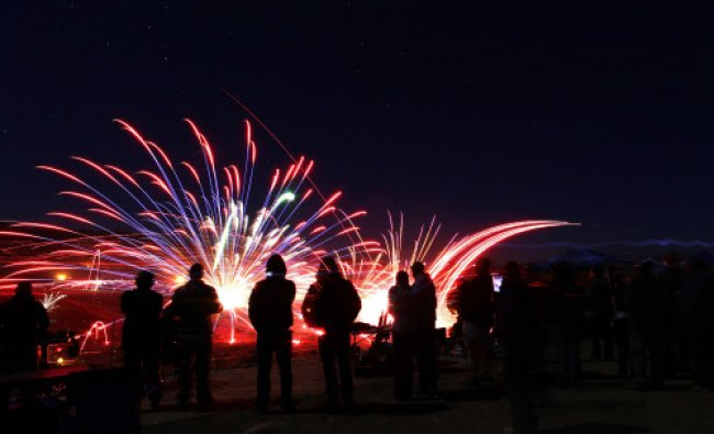 Spectators watch as fireworks used as targets are ignited by tracers from shooters firing...