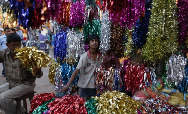 A vendor displays decorative items for sale ahead of Holi, the festival of colors...