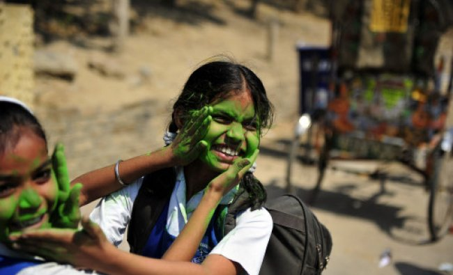 School girls play with coloured powder outside a school in Allahabad on March 25, 2013. Holi...