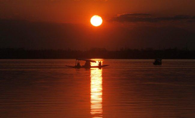 A boatman rows his boat at the Dal Lake during sunset in Srinagar, India....