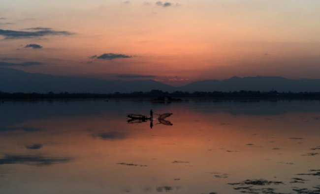 A fisherman throws a net on Dal lake at sunset in Srinagar....
