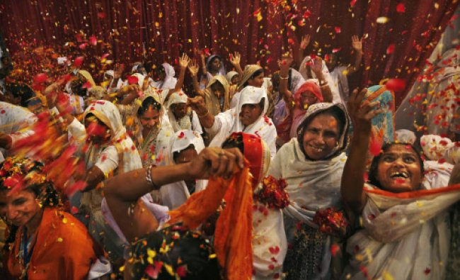 Widows throw flowers during Holi celebrations, or the festival of colors, at an event organized...