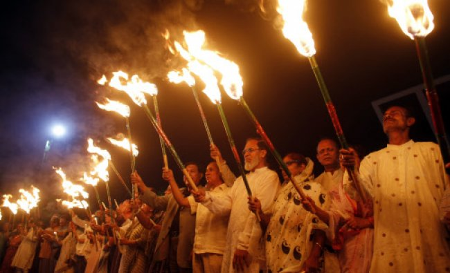 People hold lit torches during a rally to commemorate the Bangladesh Liberation War....