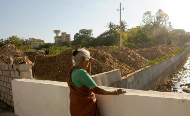 An old woman looks at the only right of way that the residents of Gouthamapura had, being blocked..