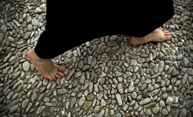 A barefoot penitent from \'Los Estudiantes\' brotherhood walks to the church before taking part...