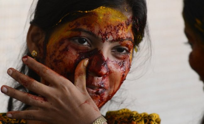 A teacher reacts after being smeared with vegetable paste made from beetroot, turmeric, spinach...