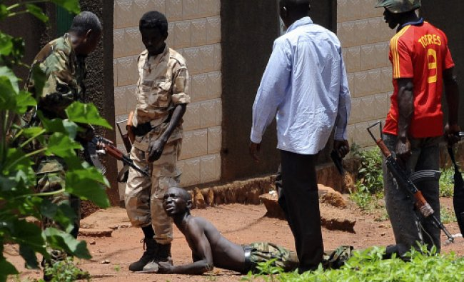 Rebels of the Seleka coalition arrest a man wearing military fatigues, claiming to also belong...