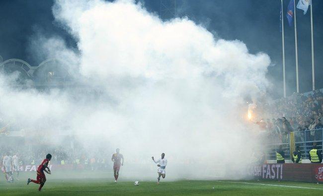 England\'s Ashley Cole (R) runs through smoke during their 2014 World Cup qualifying soccer match...
