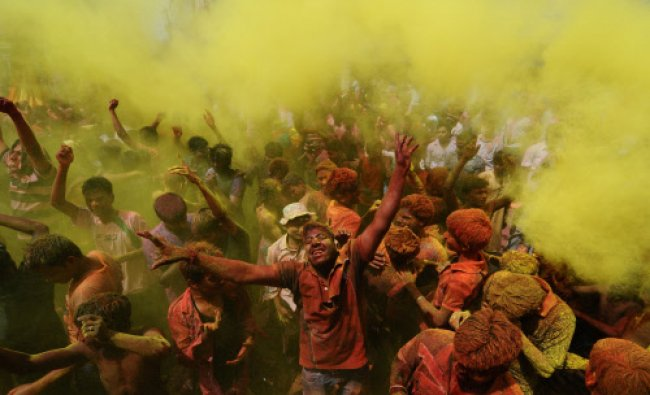 Revellers cover each other with coloured powder during Holi festival celebrations in Guwahati...