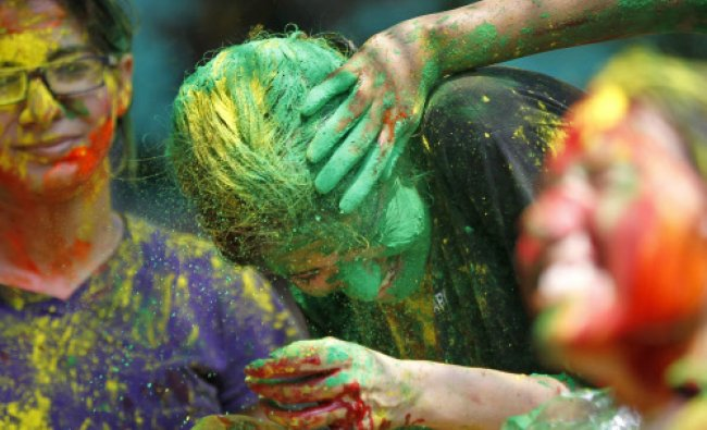 Girls, faces smeared with colored powder, celebrate the Holi festival in Mumbai...