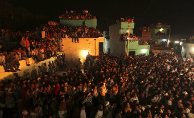Villagers watch a fire ritual before dawn from rooftops during the Holi festival in Phalen village..