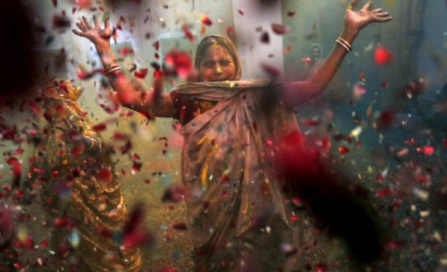 A Hindu widow throws flowers as part of Holi celebrations organized by the NGO Sulabh...