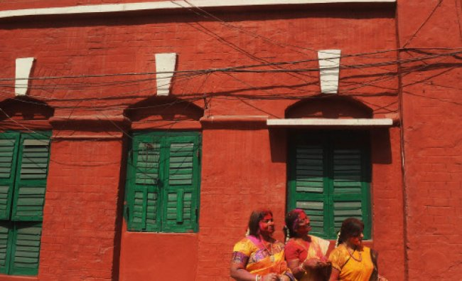 Women wait to play with coloured powder standing near a building on the side of a road during Holi..