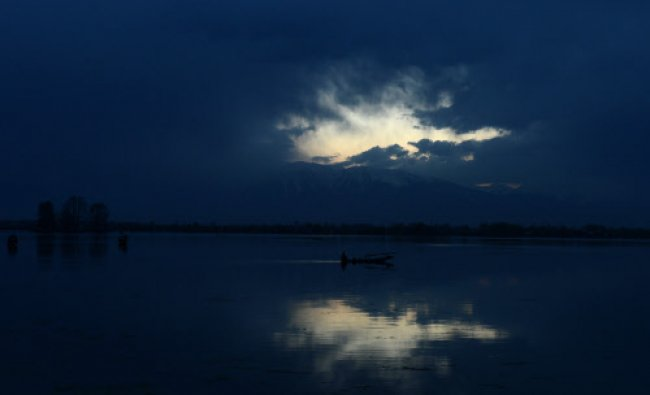 A boat sails at sunset on Dal Lake in Srinagar on March 27, 2013. Kashmir is divided between...