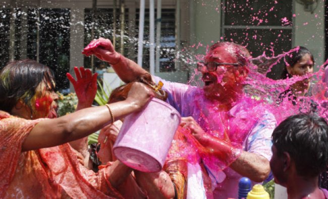 A woman pours a bucket of colored water on others during Holi celebrations in Allahabad...