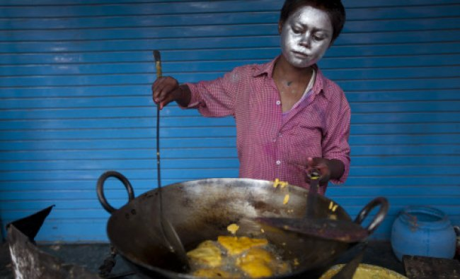 A vendor preparing snacks on the street for sale during the Hindu festival of colors...