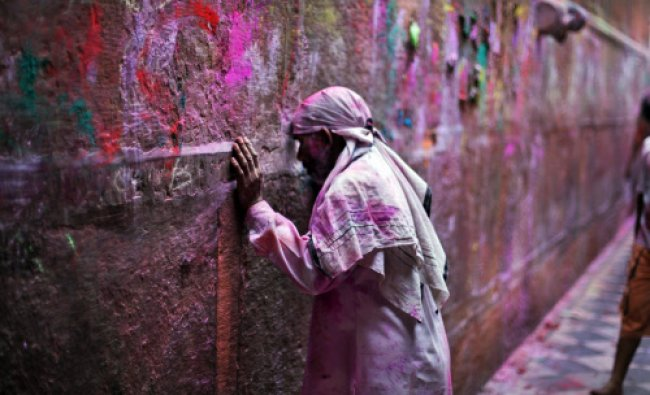 A devotee rests his forehead in an act of respect on the wall of the Banke Bihari temple during...