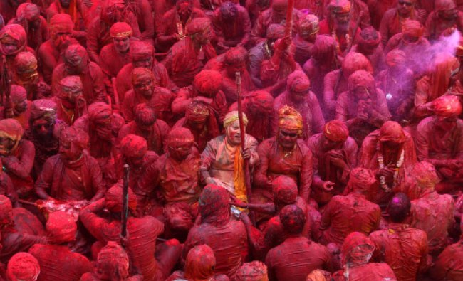 Devotees smeared with colors sing at the Nandagram temple, famous for Lord Krishna...