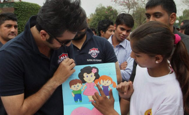 Actor Ranbir Kapoor receives a painting during a charity football match in New Delhi...