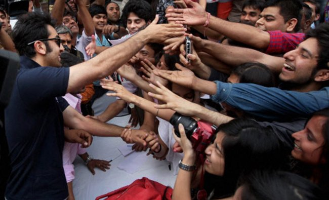 Actor Ranbir Kapoor shakes hands with his fans during a charity football match in New Delhi ...