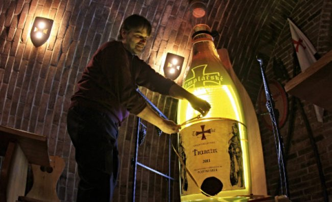 A representative of the Czech Guinness Book of Records measures a giant bottle of wine in Cejkovice.