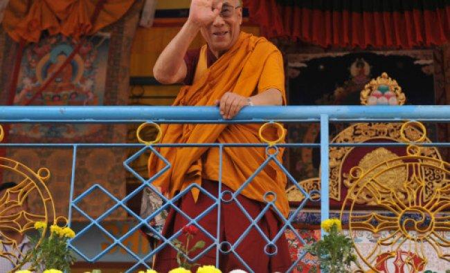 Spiritual leader the Dalai Lama greets his followers ahead of a preaching session...