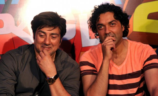 Actors Sunny Deol (L) and Bobby Deol (R) look on during the launch of the forthcoming comedy...