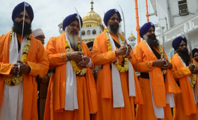 Devotees known as Punj Pyara, hold swords as they take part in a procession to mark...