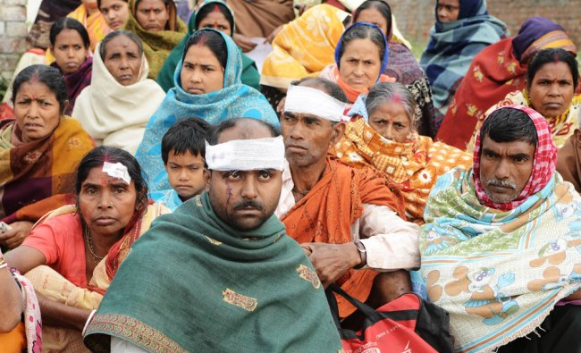Hindu pilgrims wait for transport after their bus was rammed by a large truck near Manawala village