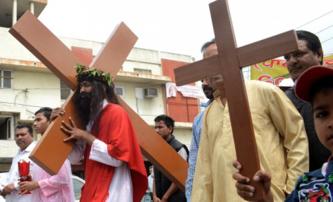 A Christian devotee portraying Jesus Christ, carries a cross as he takes part in a Good Friday...